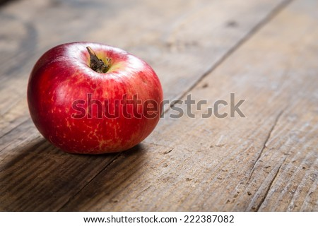 One red apple on old wooden board - stock photo