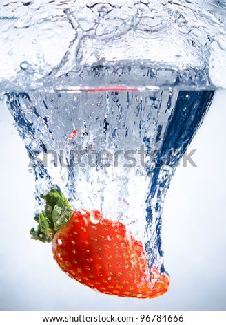 one red beauty big  strawberry  drop in blue water with splashes - stock photo