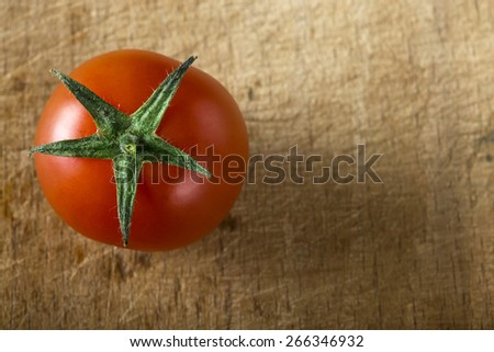 One red cherry tomato on wood background surface - stock photo