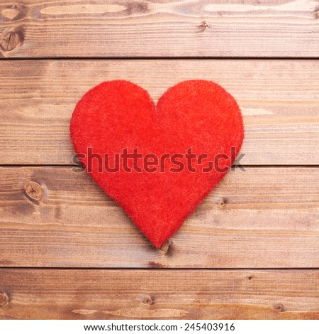 One red heart over the brown wooden boards covered surface as a love themed background composition - stock photo