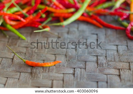 One red hot chili peppers on blurred red and green hot chili peppers background, Colorful peppers, Pepper on mat, selective focus - stock photo