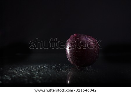 One ripe tasty beautiful seasoning fruit berry of purple wet plum with water spray lying in studio on black background, horizontal picture - stock photo