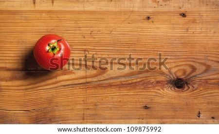 One ripe tomato on a decorative board. - stock photo