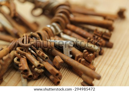 One round bunch of rusty old weathered metal door keys on old rustic wooden table background, close up, shalow dof - stock photo