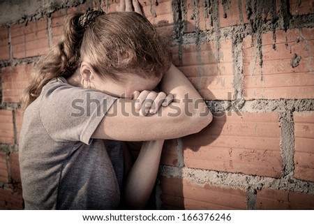 one sad woman sitting  near a brick wall - stock photo