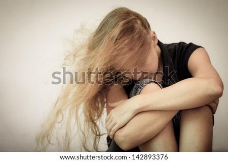 one sad woman sitting on the floor near a wall - stock photo