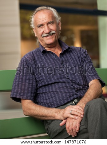 One senior man relaxes on a bench  looking at Camera