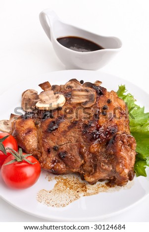 one serving of pork chop with mushrooms,  vegetables and sauce