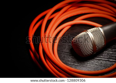 One shiny microphone and a rolled up red wire - stock photo