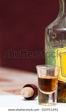 One shot, cork and bottle on table - stock photo