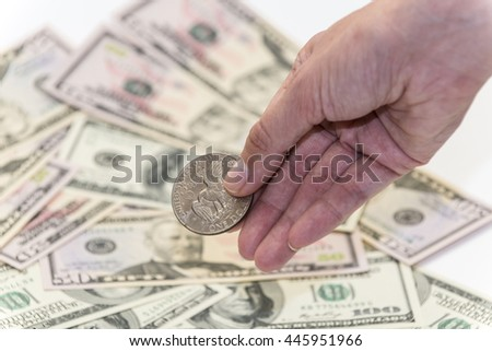 One silver dollar in her hand with hundreds and fifty banknotes as background - stock photo