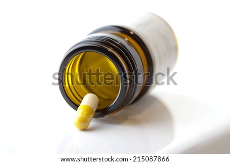 one single pill on a brown bottle,