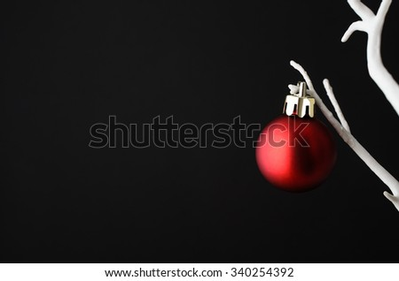 One single plain red Christmas bauble with gold clasp hanging from branch of an artificial bare white tree against black background. - stock photo