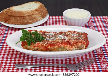 One slice of eggplant parmigiana garnished with parsley and a side of Italian bread. - stock photo