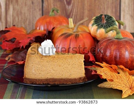 One slice of pumpkin cheesecake with whipped cream surrounding by fall decorations. - stock photo