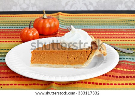 One slice of pumpkin pie garnished with whipped cream. - stock photo