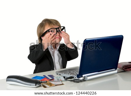 One small little girl (boy) wearing black suit with glasses, computer, credit cards and phone. Business concept. Isolated object.