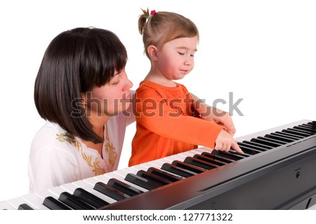 One small little girl learning to play piano with the teacher. Isolated objects. - stock photo