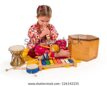 One small little girl playing on drum, flute, maraca, xylophone. Isolated object.