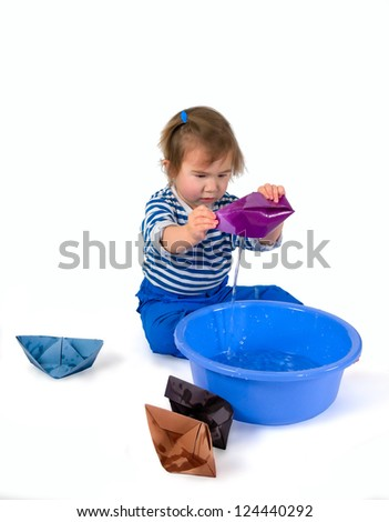 One small little girl wearing frock and blue pants playing with origami paper ships and blue basin. - stock photo