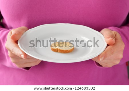 One small toast on the white plate. Small portion of food. Conceptual photo. - stock photo