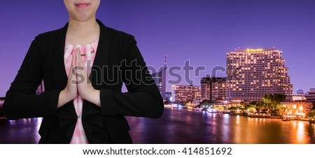 One smart business woman wear black suit with Thank You gesture stand on modern building in night light background (Business concept) - stock photo