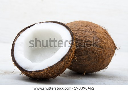One solid coconut and one coconut cracked in half - stock photo