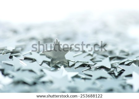 One standing star. One standing silver star among many underlying stars. Intentionally shot in high key and shallow depth of field. - stock photo