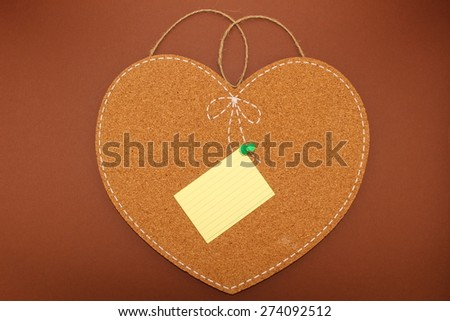 One sticky note on an isolated heart-shaped cork board