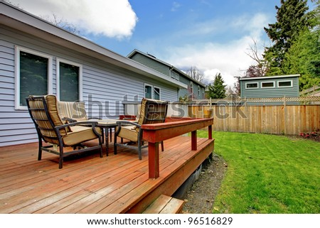 One story grey house deck with outdoor furniture and fenced back yard.
