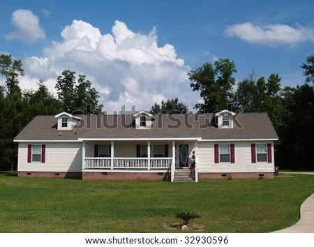 One story residential home with vinyl siding on the facade and a brick foundation. - stock photo