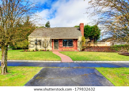 One story siding house with tile roof and brick trim. View of the front exterior , walk way and green lawn - stock photo