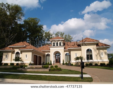 One story stucco residential home with a red clay tile roof and side garage. - stock photo