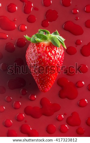 One strawberry over red background with water drops - stock photo