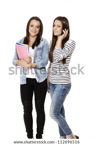 one student calling by phone near her friend with notepads on white background - stock photo