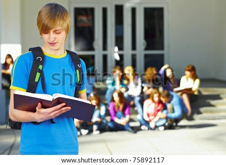 One student with book in front of group of students near the university - stock photo