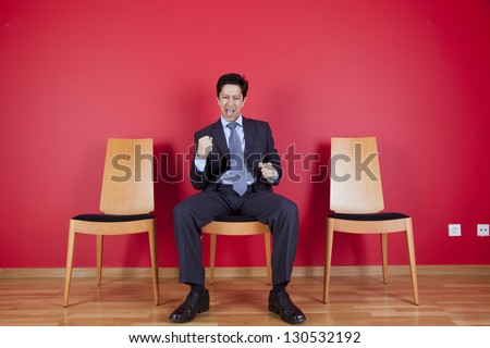 One successful businessman between two empty chairs - stock photo