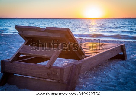 One sunbed on the beach at sunset - stock photo