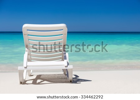 One sunbed on tropical calm beach with turquoise caribbean sea water and white sand - stock photo