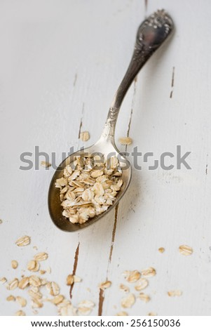 One tablespoon of oatmeal is a white wooden background. Healthy food. - stock photo