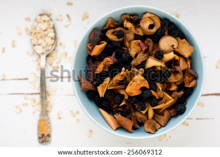 One tablespoon of oatmeal is a white wooden background near blue plate with dried apples and berries. Healthy food. - stock photo