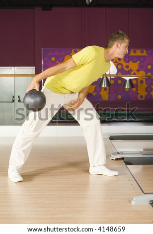 One teenage boy standing and smiling in bowling alley. Holding ball and playing. Side view