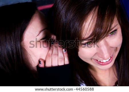One Teenage Whisper Something into the Ear of her Friend - stock photo