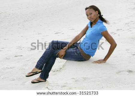 one thin African American woman model sitting on the beach with a serious expression