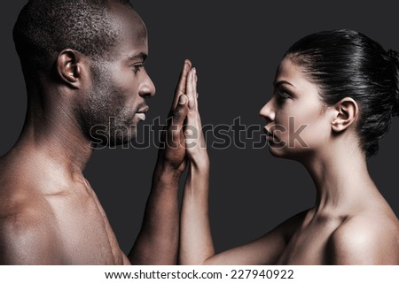 One touch and one love. Portrait of shirtless African man and Caucasian woman holding their hands clasped and looking at camera while standing against grey background  - stock photo