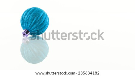 One turquoise Christmas ball isolated on white reflective background with copy space - stock photo