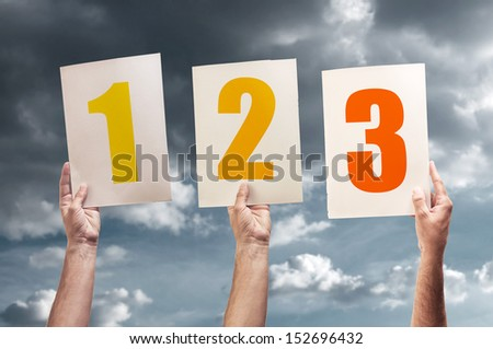 One, two and three. Hands holding papers with printed numbers. - stock photo