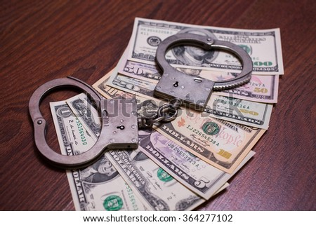 one, two, five, ten, twenty, fifty and one hundred dollar bills and handcuffs - stock photo