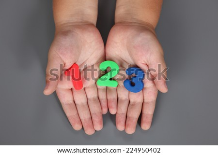 One, two, three in child's hands on grey background. - stock photo