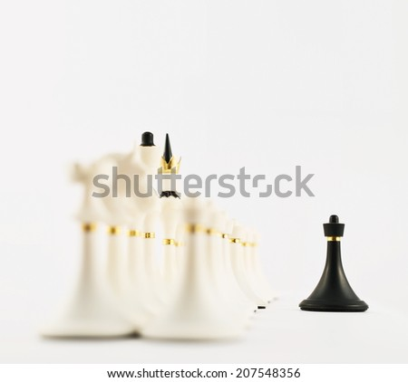 One voice against many concept as black chess pawn figure opposite to the white ones composition